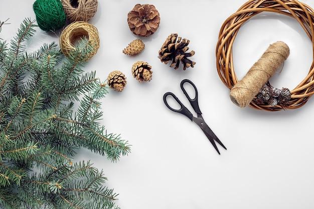 Красивая нарядная основа для венка ручной работы с тремя шишками возле нее нитками и веточками синего новогоднего ...