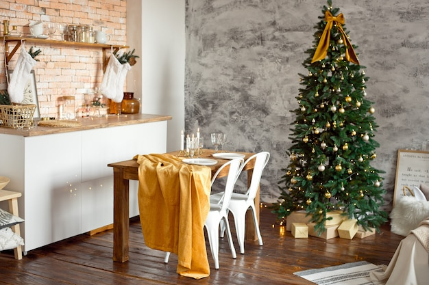 Beautiful festively decorated scandinavian-style room, a festive table with a table and a christmas tree with gifts under it.