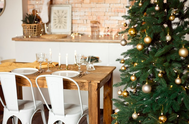 Beautiful festively decorated scandinavian-style room, a festive table with a table and a christmas tree with gifts under it