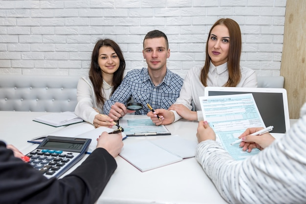 Beautiful financial consultants with 1040 tax form in office