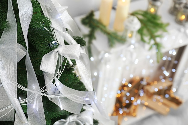 Beautiful fir tree with silver ribbons and christmas lights in room, closeup