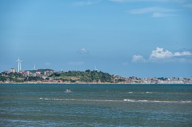 美しい漁村、青い空と白い雲、海と小さなボート