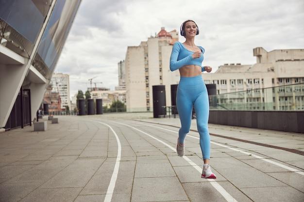 美しいフィットの白人女性が街で屋外で運動をしている