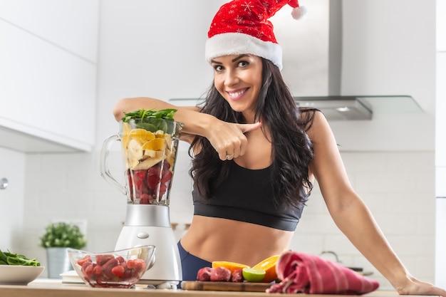 クリスマスの帽子をかぶった美しいフィットの女性は、ブレンダーで健康的な果物と野菜でいっぱいのブレンダーにもたれかかっています。