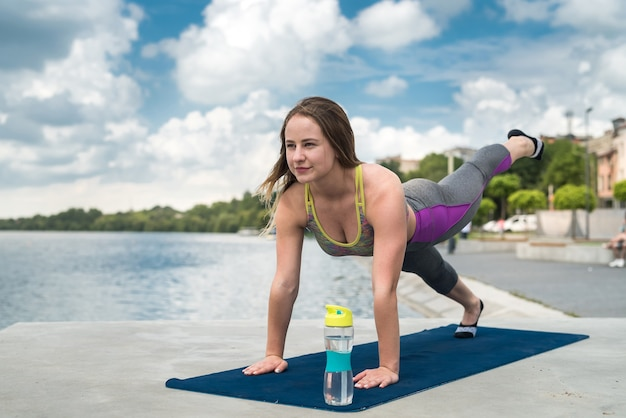 Красивая подтянутая девушка в черной спортивной одежде делает растяжку и позы йоги на коврике у озера