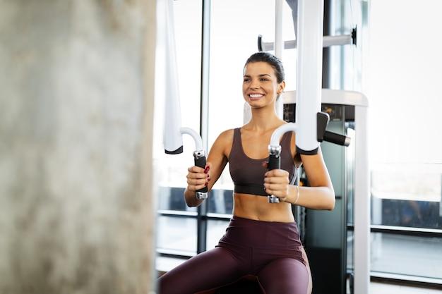 ジムでトレーニングする美しいフィットの健康な女性