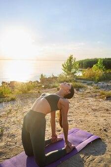 Красивая подтянутая дама в спортивных леггинсах и кроп-топе занимается йогой в солнечный день на пляже