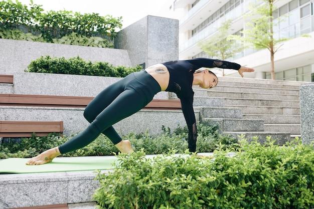 Красивая стройная стройная молодая женщина делает позу дикой вещи на открытом воздухе