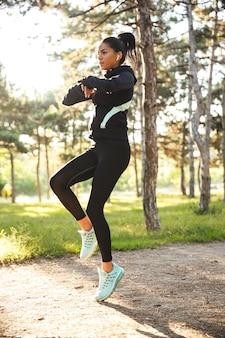 Красивая спортивная спортсменка делает разминку перед бегом в парке, прыгает, слушает музыку в наушниках