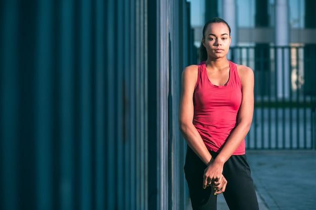 柵の近くの屋外で一人で立っている美しいフィットスポーティな女性。ウェブサイトのバナー