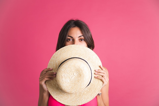 Beautiful fit tanned sporty woman in bikini and straw hat on pink