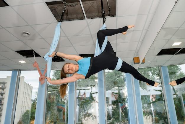 Красивая подходят женщина, практикующая аэро-йогу мухи в фитнес-студии. спортивный образ жизни для здоровья.