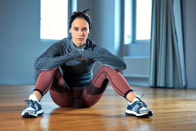 ジムの窓の前の床に座ってポーズをとるスポーツウェアの美しいフィット女性