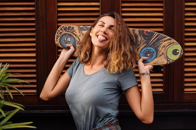 Bella donna in forma in pantaloncini di jeans, camicia a quadri con longboard