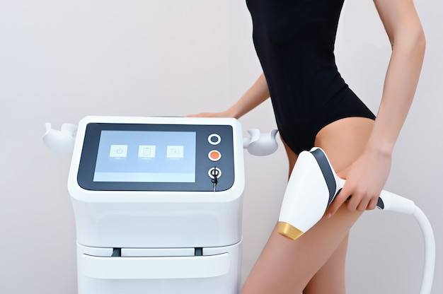 Beautiful fit woman's body with smooth soft skin in black lingerie with laser apparatus device isolated in beauty salon. hair removal and cosmetology. epilation spa concept. free space for text banner
