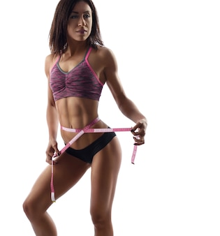 Beautiful fit woman with a measuring tape
