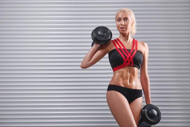 아령으로 운동하는 아름 다운 맞는 젊은 sportswoman