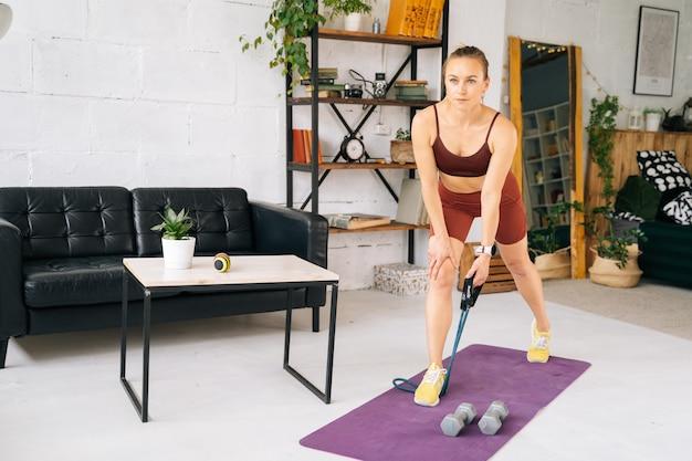 エクササイズマットに立っているストレッチラバーテープで運動するスポーツウェアを身に着けている完璧な運動体を持つ美しいフィットの若い女性。健康的なライフスタイルと家庭での身体活動の概念。
