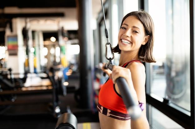 ジムで運動する美しいフィットの若い女性