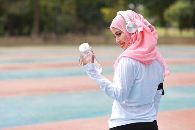 運動後の水を飲む美しいフィットネスアスリートアジアのイスラム教徒の女性