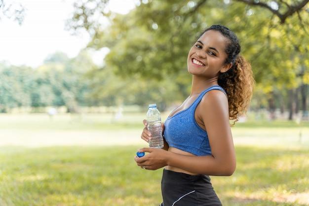 公園の屋外のポートレートでエクササイズをした後の健康のための美しいフィットネスアスリート女性飲料水