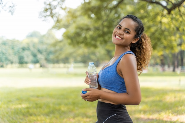 Beautiful fitness athlete woman drinking water for health after work out exercising in the park outdoor portrait