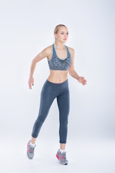 Beautiful fitness blonde girl in sports clothes runs on a gray background