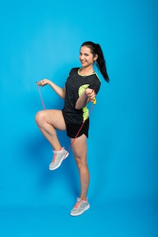 Красивая женщина фитнеса прыгает через скакалку, студия выстрел