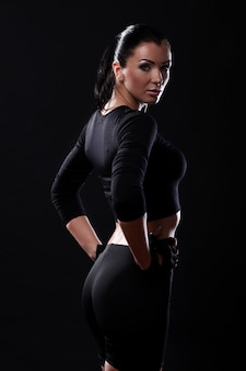 Beautiful fitness girl over black background