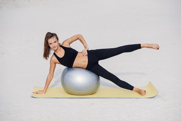 ビーチでフィットボールでピラティス演習を行う美しいフィットネス女の子。スポーツと健康的なライフスタイルのコンセプト。