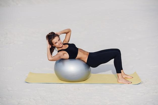 ビーチでフィットボールでストレッチ体操をしている美しいフィットネス女の子。スポーツと健康的なライフスタイルのコンセプト。ピラティスの演習を行う若い女性。