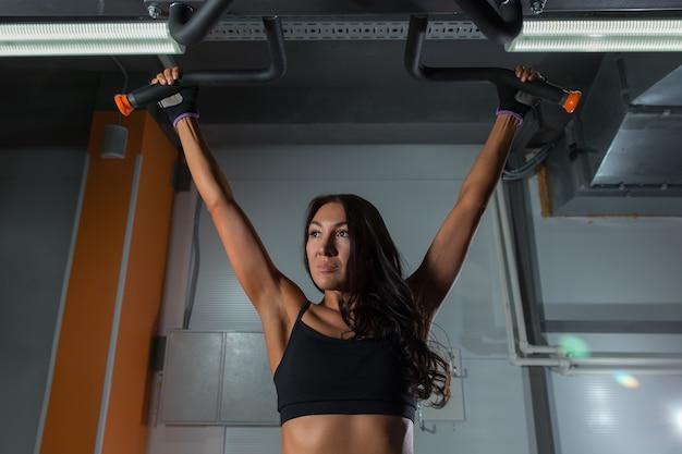 아름다운 피트니스 소녀는 스포츠 체육관의 수평 막대에서 운동을 하고 후면 모습입니다.