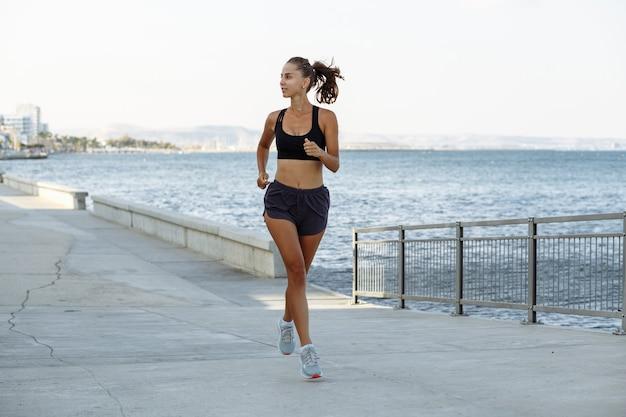 晴天の海沿いのウォーターフロントを走るショートパンツとスポーツトップの美しいフィットネスの女の子