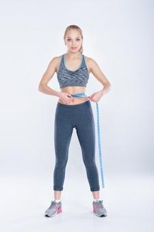 운동복을 입은 아름다운 피트니스 소녀는 회색 배경에 테이프를 측정하여 허리를 측정합니다