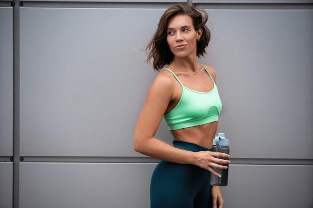 Красивая фитнес-девушка в спортивной одежде, отдыхая после тренировки, стоя на городской улице