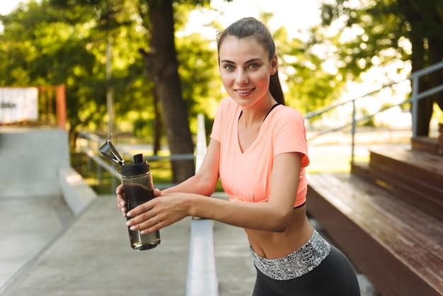 스포츠 지상에 난간에 굽힘 동안 미소하고 물병을 들고 운동복에 아름다운 피트니스 소녀