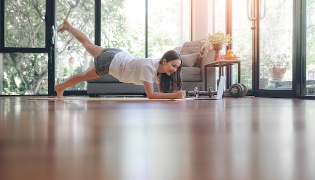아름 다운 피트 니스 소녀는 집에 머무는 동안 판자 운동을하고있다.
