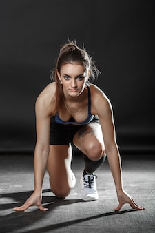 A beautiful fitness girl is sitting in run starting pose