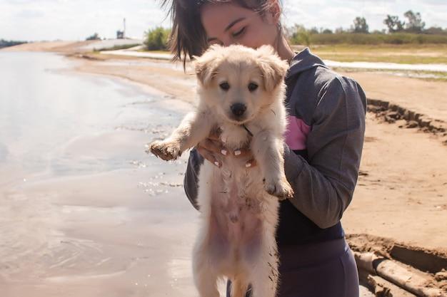 ビーチで彼女の手で子犬を持ち上げる美しいフィットネスの女の子。
