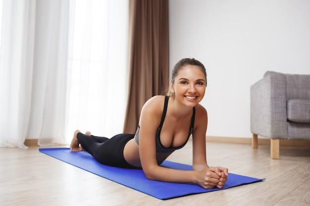 Beautiful fitness girl make sport exercises on floor