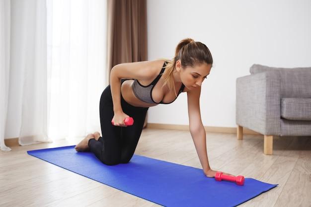 Красивая фитнес-девушка делает спортивные упражнения на полу