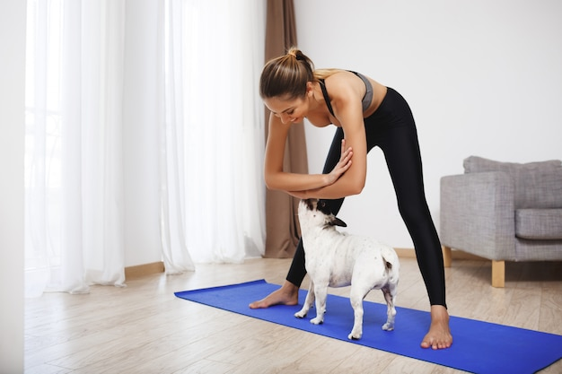 Красивая фитнес девушка делает спортивные упражнения с собакой