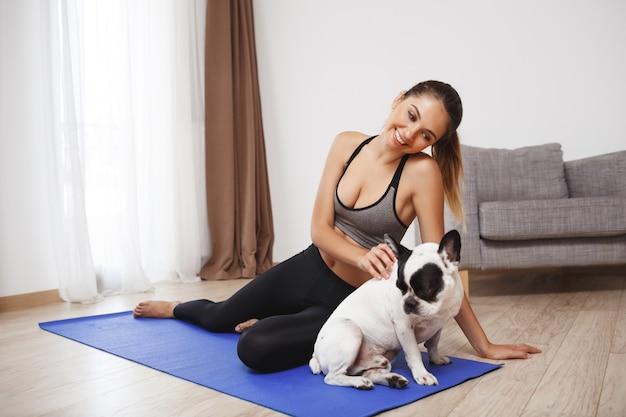 Красивая фитнес девушка сидит на полу с собакой