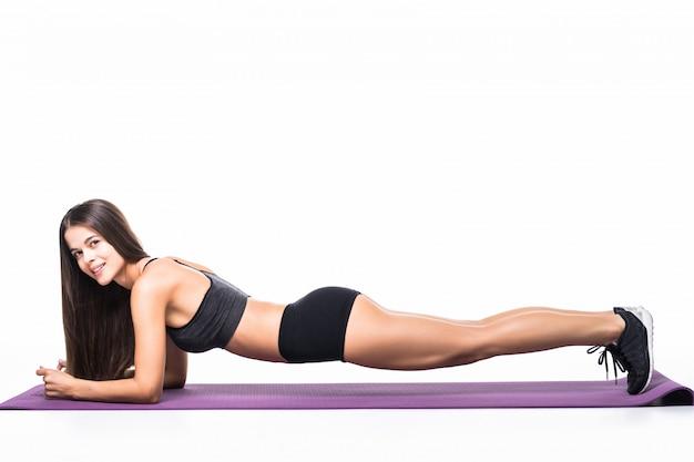 Bella ragazza di forma fisica in sportwear che si esercita facendo una plancia su bianco