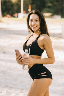 Beautiful fitness girl with long dark hair wearing in a black top and shorts listening to music with earphones in the green park