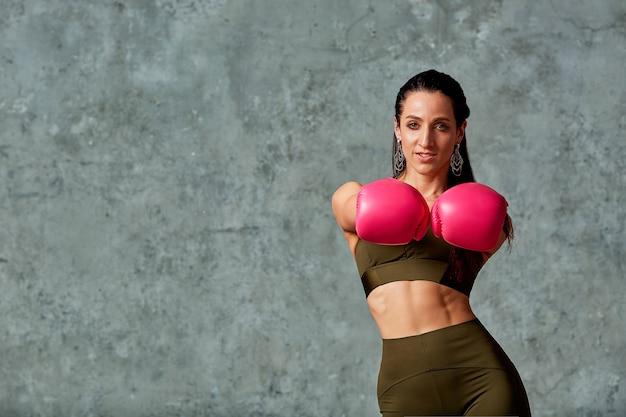 회색 배경 복사 공간, 근접 개념 스포츠 싸움 목표 달성에 분홍색 권투 장갑에 포즈를 취하는 아름다운 피트니스 라틴 소녀