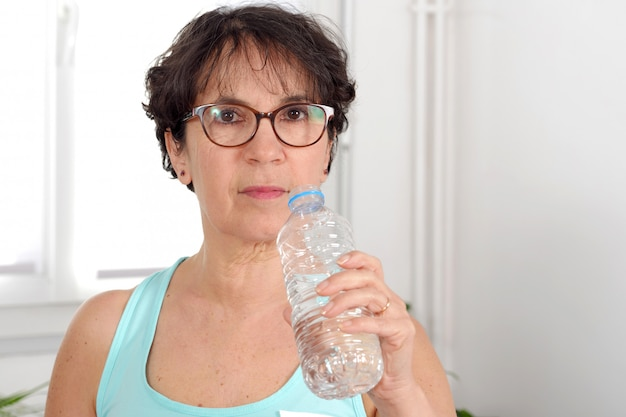 Beautiful fitness mature woman with water bottle