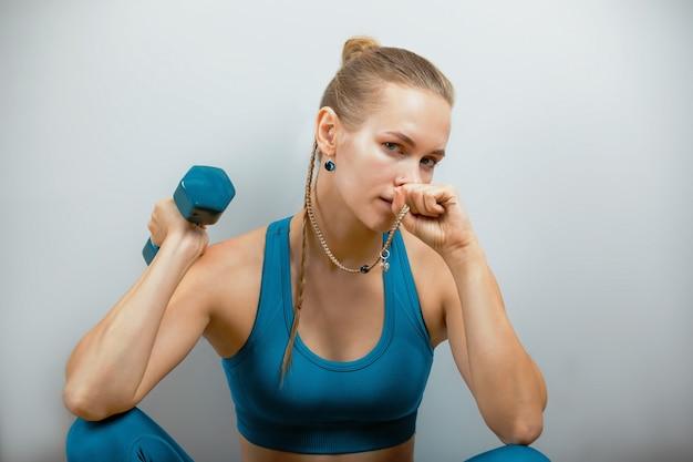 Красивая фитнес-модель делает упражнения с гантелями в руках на сером фоне