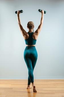 Красивая фитнес-модель делает упражнения с гантелями в руках. девушка занимается спортом в тренажерном зале на сером фоне. здоровый образ жизни. достижение целей, спортивная мотивация. скопируйте пространство.