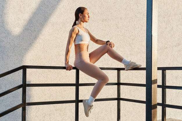 Beautiful fitness model girl posing outdoor while sitting on stair railing